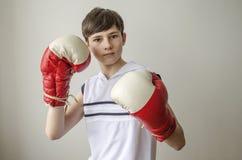 Muchacho del adolescente en una camisa blanca sin las mangas y en guantes de boxeo Fotos de archivo libres de regalías