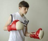 Muchacho del adolescente en una camisa blanca sin las mangas y en guantes de boxeo Fotos de archivo