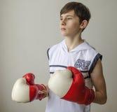 Muchacho del adolescente en una camisa blanca sin las mangas y en guantes de boxeo Imagen de archivo