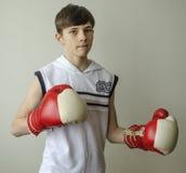 Muchacho del adolescente en una camisa blanca sin las mangas y en guantes de boxeo Imagenes de archivo