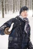 Muchacho del adolescente en una chaqueta azul, en una bufanda a cuadros y en un sombrero azul marino con un carámbano en sus mano Imagen de archivo