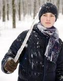 Muchacho del adolescente en una chaqueta azul, en una bufanda a cuadros y en un sombrero azul marino con un carámbano en sus mano Foto de archivo