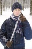 Muchacho del adolescente en una chaqueta azul, en una bufanda a cuadros y en un sombrero azul marino con un carámbano en sus mano Foto de archivo libre de regalías