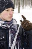 Muchacho del adolescente en una chaqueta azul, en una bufanda a cuadros y en un sombrero azul marino con un carámbano en sus mano Fotos de archivo