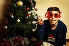 Muchacho del adolescente en vidrios frescos con el árbol de navidad Fotografía de archivo libre de regalías