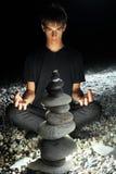 Muchacho del adolescente meditating cerca de la pirámide del guijarro Imagen de archivo libre de regalías