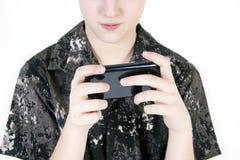 Muchacho del adolescente que busca algo en el smartphone aislado Foto de archivo libre de regalías