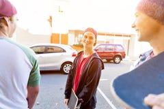 Muchacho del adolescente que camina en la calle con su monopatín Fotos de archivo libres de regalías