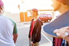 Muchacho del adolescente que camina en la calle con su monopatín Fotografía de archivo