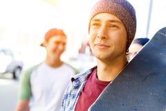 Muchacho del adolescente que camina en la calle con su monopatín Foto de archivo