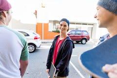 Muchacho del adolescente que camina en la calle con su monopatín Imagenes de archivo