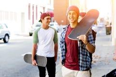 Muchacho del adolescente que camina en la calle con su monopatín Foto de archivo libre de regalías