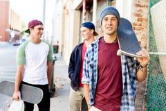 Muchacho del adolescente que camina en la calle con su monopatín Imágenes de archivo libres de regalías