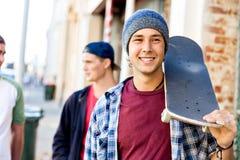 Muchacho del adolescente que camina en la calle con su monopatín Fotos de archivo