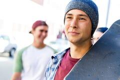 Muchacho del adolescente que camina en la calle con su monopatín Fotografía de archivo libre de regalías