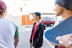 Muchacho del adolescente que camina en la calle con su monopatín Imagen de archivo libre de regalías