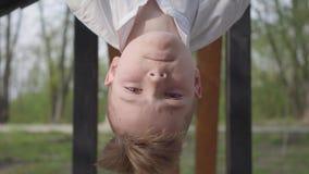 Muchacho del adolescente que cuelga su cabeza abajo de la barra horizontal y que sonríe en el fondo del parque de la primavera metrajes
