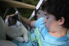 Muchacho del adolescente que duerme con el gato en sillón de la calesa del verano Foto de archivo