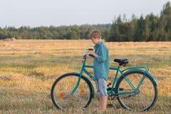 Muchacho del adolescente que empuja la bicicleta en campo de granja Fotografía de archivo