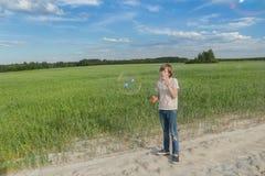 Muchacho del adolescente que hace burbujas de jabón en el camino polvoriento del campo de granja de la suciedad Fotografía de archivo
