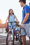 Muchacho del adolescente que infla el neumático de la bici para ayudar a su amigo femenino Imagen de archivo