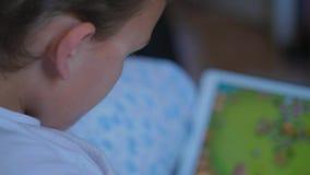 Muchacho del adolescente que juega al juego en la tableta, pantalla táctil, parte posterior almacen de metraje de vídeo