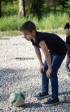 Muchacho del adolescente que juega en el fútbol de la yarda que se prepara para golpear la bola con el pie Imagen de archivo libre de regalías