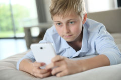 Muchacho del adolescente que juega en smartphone Imágenes de archivo libres de regalías