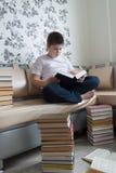 Muchacho del adolescente que lee un libro en sitio Imagen de archivo libre de regalías