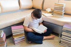 Muchacho del adolescente que lee un libro en sitio Imagenes de archivo