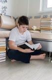 Muchacho del adolescente que lee un libro en sitio Foto de archivo