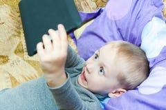 Muchacho del adolescente que miente en la cama con un Tablet PC Fotografía de archivo