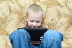 Muchacho del adolescente que miente en la cama con un Tablet PC Foto de archivo