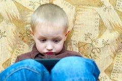 Muchacho del adolescente que miente en la cama con un Tablet PC Imagen de archivo