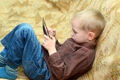 Muchacho del adolescente que miente en la cama con un Tablet PC Imagen de archivo libre de regalías