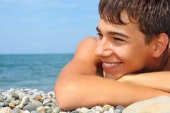 Muchacho del adolescente que miente en la costa pedregosa, mirando lejos Imágenes de archivo libres de regalías