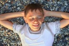 Muchacho del adolescente que miente en las piedras, ojos cerrados Imagen de archivo