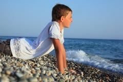 Muchacho del adolescente que miente en piedras en la costa Fotografía de archivo libre de regalías