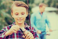 Muchacho del adolescente que mira pescados en el gancho Imagenes de archivo