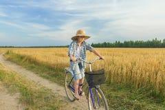 Muchacho del adolescente que monta una bicicleta en la carretera nacional Imagen de archivo libre de regalías