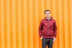 Muchacho del adolescente que presenta sobre fondo de la naranja del contraste; copyspace Imagen de archivo