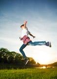 Muchacho del adolescente que salta en el parque en la puesta del sol Imagen de archivo libre de regalías