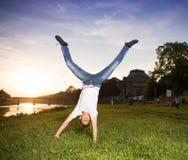 Muchacho del adolescente que salta en el parque en la puesta del sol Imagenes de archivo
