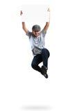 Muchacho del adolescente que salta y que sostiene el papel en blanco Imágenes de archivo libres de regalías