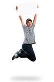 Muchacho del adolescente que salta y que sostiene el papel en blanco Fotografía de archivo