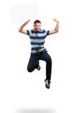 Muchacho del adolescente que salta y que sostiene el papel en blanco Foto de archivo
