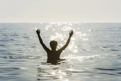 Muchacho del adolescente que se baña en el mar con sus brazos aumentados Fotografía de archivo libre de regalías