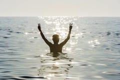 Muchacho del adolescente que se baña en el mar que hace la muestra de la victoria Imágenes de archivo libres de regalías