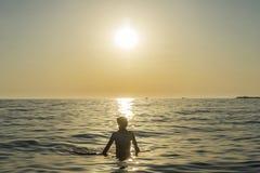 Muchacho del adolescente que se baña en el mar en la puesta del sol en Sicilia Fotos de archivo