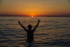 Muchacho del adolescente que se baña en el mar en la puesta del sol en Sicilia foto de archivo